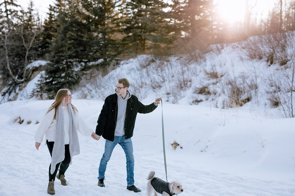 A close up of a couple walking in the snow with their dog.