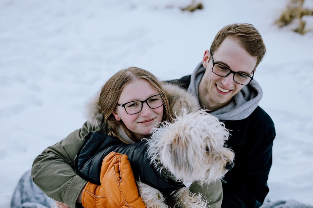 An engagement photo of a couple with their dog.